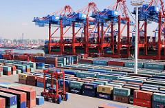Frachtschiff unter den Containerbrücken am Kai des TErminal Eurogate - Portalhubwagen im Containerlager in Hamburg Waltershof.