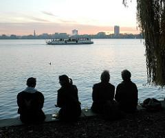 Abend an der Alsterperle - Gäste des Uhlenhorster Treffpunkts Alsterperle sitzen mit einem Getränk auf der Ufermauer der Aussenalster - im Hintergrund die Skyline Hamburgs - der historische Alsterdampfer St. Georg fährt auf seinem Dämmertörn auf der