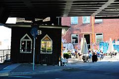 Oberhafenkantine an der Oberhafenbrücke - Gäste an den Tischen auf dem Vorplatz / Gehweg - Bilder aus dem Hamburger STadtteil Hafencity.