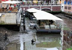 Wg. des geplanten Baus einer Fischtreppe an der Rathausschleuse wird das Alsterfleet trockengelegt - so ist auch das Wasser im Bleichenfleet abgelassen. Das Restaurant auf den Pontons liegt auf dem Trockenen - zwei Taucher sind im Schlamm.