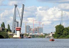 Blick vom Reiherstieg zur Baustelle der Elbphilharmonie; ein Sportboot fährt Richtung Rethe, die Reiherstiegklappbrücke ist hochgeklappt.