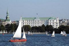 Blick über die Aussenalster nach Hamburg St. Georg. Boote segeln auf der Alster - im Hintergrund das Gebäude des Hotel Atlantic und der Kirchturm der Hl. Dreieinigkeitskirche vom Stadtteil.