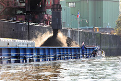 Der Frachtraum des Binnenschiffs ist mit Schüttgut gefüllt - das Schiff liegt tief im Wasser des Sandauhafens in Hamburg Altenwerder.