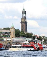 Blick über die St. Pauli Landungsbrücken zur St. Michaeliskrirche in der Neustadt Hamburgs. Auf der Elbe fährt eine vollbesetzte Hafenfähre Richtung Altona.