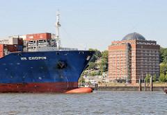 Bug des Containerschiff HS CHOPIN auf der Fahrt in den Hafen Hamburgs - an Land das zu einer Seniorenresidenz umgebaute Neumühlener Kühlhaus.