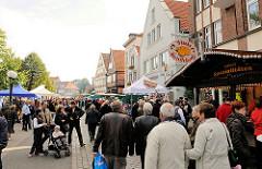 Stände auf dem Bergedorfer Landmarkt in der Alten Holstenstrasse. BesucherInnen schlendern an den Ständen in der Bergedorfer Innenstadt vorbei.