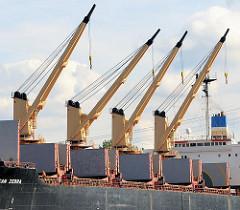 Vier Ladekräne an Bord eines Frachters am Rosskai im Rosshafen von Hamburg Steinwerder - die Ladeluken des Frachtschiffs sind geöffnet.