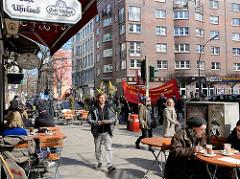 Demonstrationszug vom Hamburger Ostermarsch in der Langen Reihe in Hamburg St. Georg - Demonstranten auf der Strasse - Gäste in Strassencafes in der Sonne.