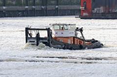 Schubschiff als Eisbrecher im Hamburger Hafen - eisbedeckte Elbe in Hamburg; das Schiff schiebt die Eisschollen vor sich her.