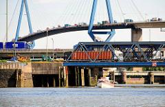Blick vom Waltershofer Hafen auf die Köhlbrandbrücke - eine Barkasse fährt in das Hafenbecken ein; im Hintergrund die Schleusentore der Rugenberger SChleuse.