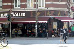 Eckkneipe, Restaurant Frau Möller in Hamburg St. Georg - Tische mit Gästen auf dem Fussweg unter Markisen.