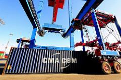Der Container wurde abgesetzt, der Fahrer eines Portalhubwagens fährt über den Container, um die Metallbox weiter zu transportieren.