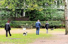Platz im Hölderlinspark der Hamburger Jarrestadt - SpaziergängerInnen mit ihren Hunden nutzen die Grünfläche.