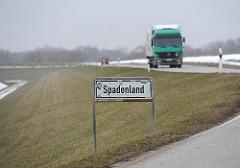 Grenzschild des Stadtteils Spadenland - Lastwagen auf der Deichstrasse.