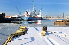 Alte Hafenrelikte an einer Kaimauer im teilweise zugeschütteten Hamburger Südwesthafen - Dalben und Prellbock eines ehem. Hafenkrans - Frachtschiff am Afrikakai - beladene Schuten am Togokai. Auf der gegenüberliegenden Seite der Norderelbe Neubauten