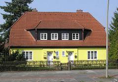 Doppelhaus in der Hamburger Schumacher Siedlung - Tangstedter Landstrasse, Hamburg Langenhorn. Wohnhaus mit gelber Fassade.