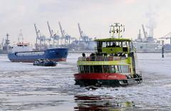 Schiffsverkehr auf der Elbe im Winter - Eisgang im Hafen Hamburgs - Hafenfähre und Frachtschiffe.
