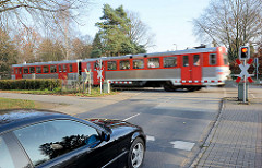 Geschlossene Bahnschranken am Harksheider Weg in Quickborn; wartendes Auto, fahrender AKN-Zug.