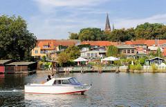 Sportboot in Fahrt auf dem Malchower See - im Hintergrund der Kirchturm der Stadtkirche von Malchow.