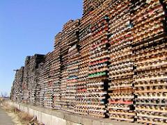Gestapelte Holzpaletten auf einer Rampe vor einem Lagerschuppen am Versmannkai im Baakenhafen - Bilder aus dem Hafen Hamburgs.