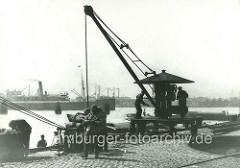 Handkran am Sandtorhöft; eine Ladung Kohlensäcke wurde an Land gebracht und liegt auf einer Waage - Kohlenträger am Kai.  ( ca. 1905 )