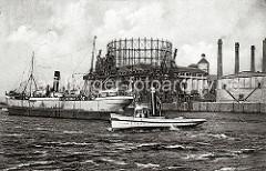Ein Schlepper mit hohem Schornstein überquert die Elbe beim Gaswerk Grasbrook - ein Frachtschiff hat im Strom an den Dalben fest gemacht. Im Hintergrund die Krananlagen am Kai des Hamburger Gaswerks auf dem Grasbrook. (ca. 1916)