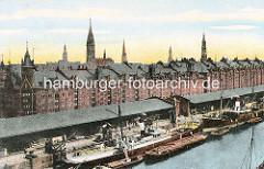 Blick auf die Kaianlagen im Sandtorhafen - Sandtorkai im historischen Hamburger Hafen - Dampfschiffe liegen am Kai, sie werden über Kräne be- und entladen. Auf der Wasserseite Kähne und Schuten - im Hintergrud die Speichergebäude der Hambu