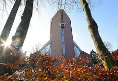 Die 2000 geweihte St. Marienkirche in Quickborn - Gegenlichtaufnahme, Herbstlaub an einer Buchenhecke.
