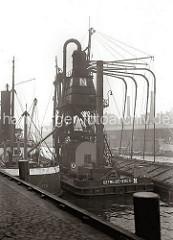 Der pneumatische Getreideheber saugt das Getreide mittels eines Luftstroms über die Saugleitungen aus dem wasser- seitig liegenden Binnenschiff in ein Behältnis des Hebers. (ca. 1934)