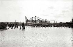 Im Seehafen wird die Fracht eines Kohlenfrachters gelöscht - ein Elbkahn liegt längsseits, der Laderaum ist aufgedeckt. Hinter den Holzdalben sind die Halbportalkräne am Kai zu erkennen. (ca. 1938)