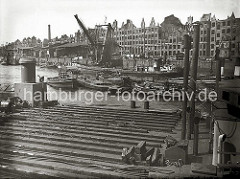 Mit Hilfe von Schuten und Barkassen wird eine durch Kriegseinwirkungen ins Hafenwasser gestürzte Lokomotive der Hafenbahn im Sandtorhafen zum Schwimmkran geschleppt. Am Sandtorkai liegen Arbeitsboote. (1948)