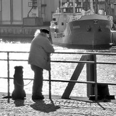 Mann mit Hund blickt über den Hafen von Neustadt in Holstein; das Frachtschiff Pavona liegt am Kai.