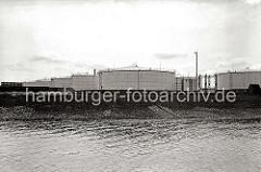 Blick über das geböschte Ufer der Süderelbe auf die Öltanks des Öllagers im Harburger Hafen. (ca. 1938)
