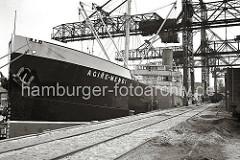 Die Kohlenfracht des Seeschiffs AGIRE-MENDI wird im Seehafens Harburg gelöscht. Auf dem Kai die auf Rädern laufenden Krananlagen, die die Kohle an Land transportieren und gleich in die Güterwaggon verladen. (ca. 1938)