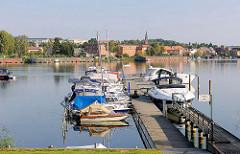 Bootssteg mit Sportbooten - Blick über den Malchower See; Bootshäuser und histoirische Industriearchitektur an der Mühlenstrasse.