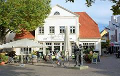 Am Markt von Neustadt in Holstein, historisches Wohnhaus / Geschäftshaus, jetzt Café / Restaurant mit Aussengastronomie; Bronzeskulptur Fischer von Serge Mangin.
