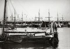 Ein Holzewer hat an einer Dalbe in der Norderelbe festgemacht; die Schiffer stehen im Heck des Bootes beim Steuerruder; ein weiterer Ewer segelt auf der Elbe, ein Ruderboot im Schlepptau. Im Hintergrund die Kaischuppen am Strandkai, Frachtsegler