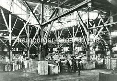 Ausfuhrschuppen im Magdeburger Hafen in der Hansestadt Hamburg - Sammelstelle für Waren die exportiert werden sollen. Hohes helles Lagergebäude mit Holzkonstruktion - Lagerarbeiter mit Karre, Holzkisten in unterschiedlichen Größen. (ca. 1905)