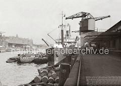 Die Ladung Fässer eines Frachtschiffs am Kaiserkai des Sandtorhafens wird gelöscht - mit den Halbportalkränen werden die Holztonnen an Land gebracht - sie liegen auf der Laderampe und sind auf einem Güterwaggon gestapelt. (ca. 1934)