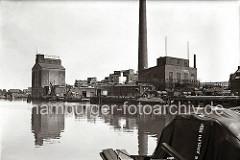 """Fabrikationsanlage mit Silo und hohem Schornstein der """"Thörl's Vereinigte Harburger Ölfabriken AG"""" im Harburger Überwinterungshafen. Fässer liegen auf dem Kai, eine Schute wird über eine Kippvorrichtung beladen. (ca. 1938)"""