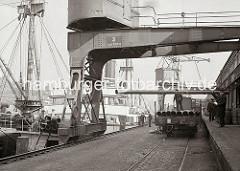 Am Haken des Halbportalkrans hängt ein langes Eisenrohr, das gerade von einem offenen Güterwaggon abgeladen worden ist. An Deck des Frachters am Kaiserkai sind weitere Rohre gelagert. (ca. 1934)
