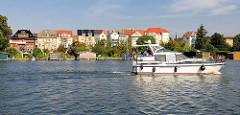 Motorboot in Fahrt auf dem Malchower See - im Hintergrund Wohnhäuser.