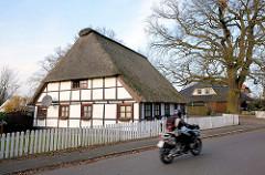 Reetdachkate mit Fachwerk; Motorradfahrer - Pinneberger Strasse in Quickborn.
