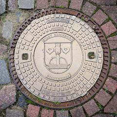 Gusseiserner Gullideckel der Stadt Quickborn / Stadtwerke; Wappen der Stadt, Brunnen mit Eule, zwei Seeblätter.