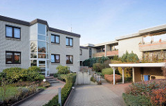 Neubauten mit verglasten Treppenhaus; Balkons in der Sonne - Carport / Architektur in Quickborn, Kreis Pinneberg.
