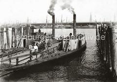Die Dampffähre über die Norderelbe hat an der Anlegestelle Grosser Grasbrook angelegt - die Rampe ist herunter gelassen; eine zweiachsige Herrenkutsche, die ein Schimmel zieht, wird zur Abfahrt vorbereitet. ( ca. 1905 )