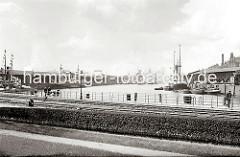 Blick in den Sandtorhafen Richtung Elbe / Kaispeicher A - links der Kaiserspeicher und rechts der Sandtorkai. Eine Familie mit Kinderwagen geht auf dem Kai. (ca. 1934)