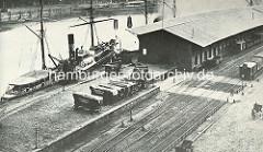 Ein Frachtschiff liegt am Kaiserkai des Hamburger Sandtorhafens - Pferdewagen mit Plane abgedeckt - Eisenbahnschienen und Waggons vor dem Lagerschuppen. ( ca. 1875 )