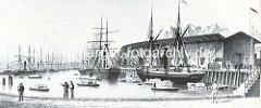 Blick auf den Sandtorkai im neu gebauten Sandtorhafen - Segelschiffe liegen am Kai, Schuten und Kähne transportieren Lasten über das Hafenbecken - hoher Lagerschupen mit Laderampe. ( ca. 1866 )