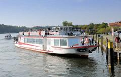 Ein Fahrgastschiff / Ausflugsschiff legt vom Anleger in Malchow ab -  Touristen sitzen in der Sonne auf dem Oberdeck.